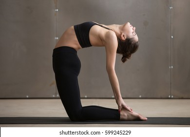 Young attractive yogi woman practicing yoga, doing Ustrasana exercise, Camel pose, working out, wearing black sportswear, cool urban style, full length, grey studio background, side view