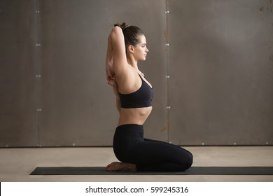 Young attractive yogi woman practicing yoga, sitting in Vajrasana pose with hands hooked behind the back for Triceps stretch, working out wearing black sportswear, cool urban style studio, full length