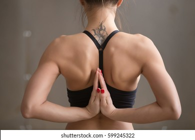 Young attractive yogi woman practicing yoga, making Namaste behind the back, working out, wearing black sportswear, cool urban style, grey studio background, rear view, closeup, tattoo on her neck
