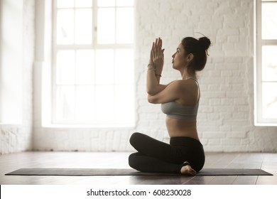 Young attractive yogi woman practicing yoga concept, sitting in Gomukasana exercise, Cow Face pose, working out, wearing sportswear, full length, white loft studio background, side view portrait