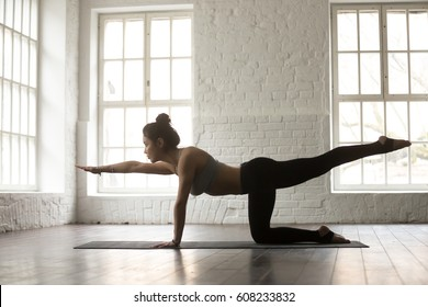 Young attractive yogi woman practicing yoga concept, standing in Bird dog exercise, Donkey, Kick pose, working out, wearing black sportswear, full length, white loft studio background, side view
