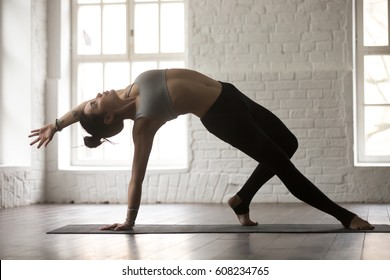 Young attractive yogi woman practicing yoga concept, standing in Camatkarasana exercise, Wild Thing, Flip-the-Dog pose, working out, wearing sportswear, full length, white studio background, side view