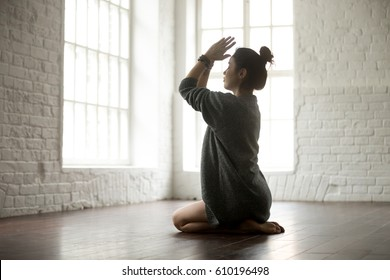 Young attractive yogi woman practicing yoga concept, sitting in vajrasana exercise, seiza pose, working out on the floor, wearing grey oversized sweater, full length, white loft studio background