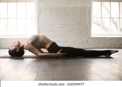 Young attractive yogi woman practicing yoga concept, stretching in Matsyasana exercise, Fish pose, working out, wearing sportswear, full length, white loft studio background. Side view