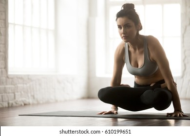 Young attractive yogi woman practicing yoga concept, standing in Tolasana exercise, Scale pose, working out, wearing sportswear bra and pants, full length, white loft studio background