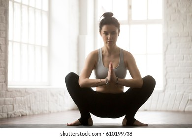 Young attractive yogi woman practicing yoga concept, sitting in Malasana exercise, Garland pose, working out, wearing sportswear, full length, white loft studio background