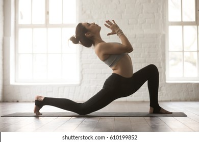 Young attractive yogi woman practicing yoga concept, standing in anjaneyasana exercise, Horse rider pose, working out, wearing sportswear bra and pants, full length, white loft studio background