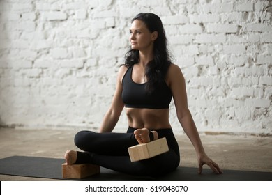Young attractive yogi woman practicing yoga concept, sitting in Agni stambhasana exercise, Fire Log, Ankle to Knee pose, using wooden block, working out, full length, white loft studio background