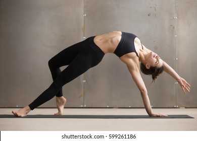 Young attractive yogini woman practicing yoga, stretching in Camatkarasana exercise, Wild Thing, Flip-the-Dog pose, working out, wearing black sportswear, cool urban style, full length, grey studio