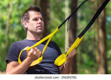 Young attractiveman does suspension training with fitness straps outdoors in the nature.