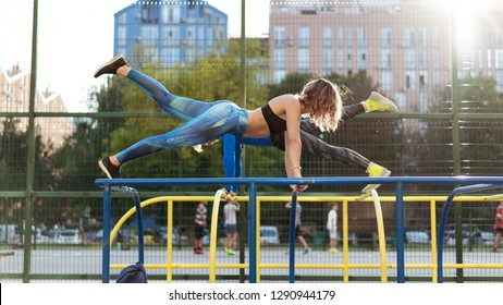 Young attrective crossfit man and woman working out on the sportsground. Making plank on the parallet bars with raised leg