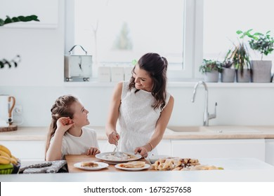 Young au pair making pancakes, cooking, baking in the white kitchen with a little girl