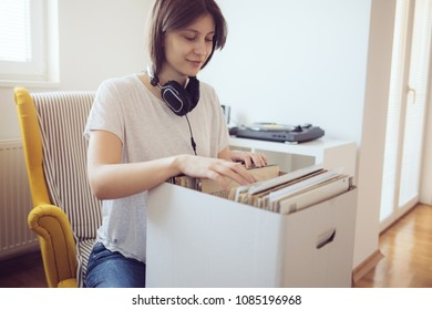 Young audiophile browses through a selection of vintage records. Young woman searching music albums
