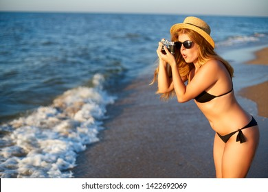 Young authentic woman with vintage retro film camera enjoying tropical beach on summer vacation. Female travel photographer in straw hat taking photos having fun at sea. Real girl unretouched shape.