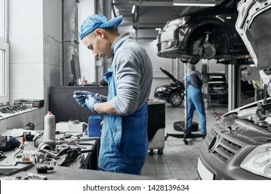 Young auto mechanic in blue and dirty overalls working near black car with opened hood is going to change old spark plugs in car engine. Qualified repairman fixing vehicle's motor in service station