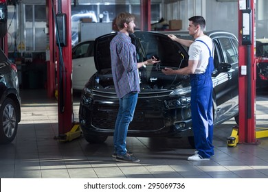 Young automotive technician talking with male client