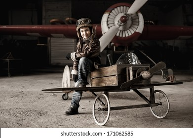 Young Aviator in a homemade aircraft in a hangar with these planes