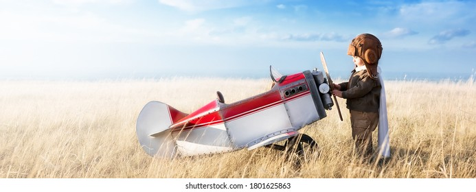 Young aviator with model airplane in the field on a sunny day