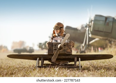 Young Aviator sits in his makeshift toy airplane on airport parking