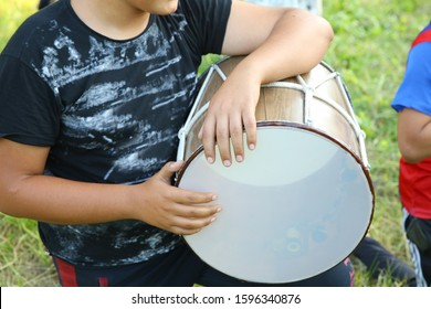 Young azeri guys playing traditional drum nagara on the holiday of Novruz . The national instrument of Azerbaijan nagara . children in national costumes play drums
