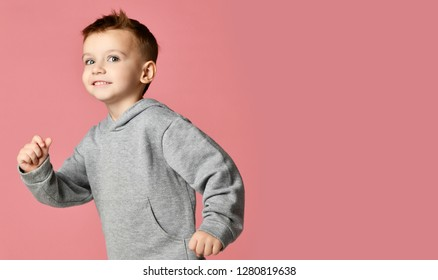 Young baby boy kid in grey hoodie with free text copy space running happy smiling on pink background