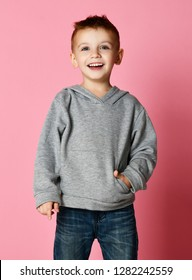 Young baby boy kid in grey hoodie with free text copy space happy smiling on pink background