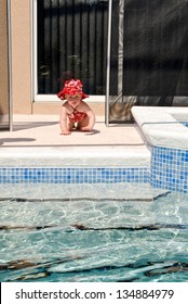 A young baby crawls through the opening of the safety fence left open. No adults appear to be near the child as she moves toward the swimming pool.