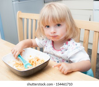 Young baby feeding herself in the family home.