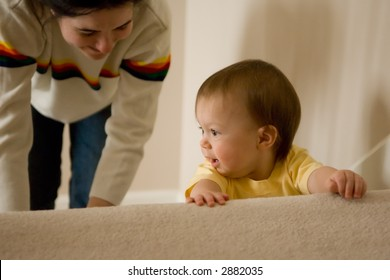 Young baby girl playing on the stairs, mother is near by helping her learn to climb the stairs safely. Lifestyle image.