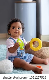 Young baby girl playing with toys at home in nursery with copy space, childhood development and curiousity
