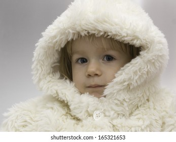 Young baby girl wearing a white snowsuit