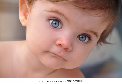 A young baby is looking at the camera with blue eyes. Use it for a child or parenthood concept.