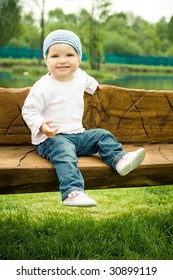 young baby sits on a wooden bench