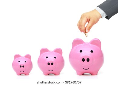 Young baby's hand in businessman suit giving golden coin to three piggy banks with different sizes