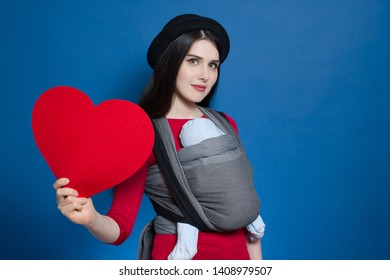 Young babywearing mother and baby in woven wrap, front wrap cross carry, big fleece heart in hand. Love babywering concept
