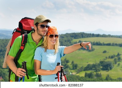Young backpack couple with hiking poles beautiful panoramic view countryside