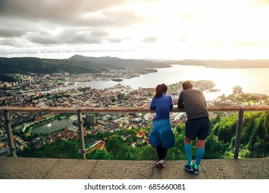 Young backpack couple (lover) standing for seeing cityscape and seascape with beautiful view and gold light sky and cloud background near sunset time of Floyen Mountain, Bergen, Norway.