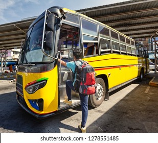 Young backpack traveler getting into bus. Local bus in Karnchanaburi province, Thailand.