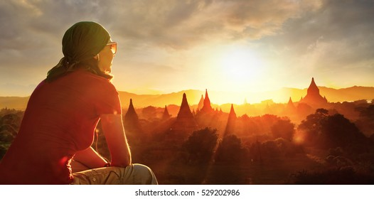 Young backpacker enjoying a temples at Bagan Myanmar Asia at sunset view from top of a temple.