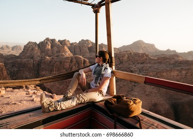 Young backpacker girl relaxing in The Lost City of Petra during beautiful sunset