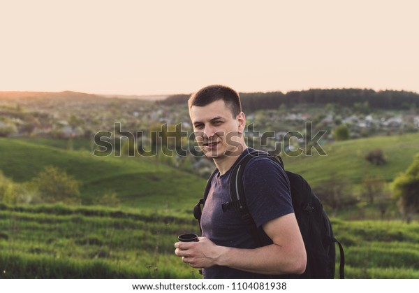 Young backpacker looking into the camera and holding the thermal cup filled with coffee. Concept of the lunch in journey, traveling, journey, hiking, backpacking.