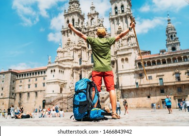 Young backpacker man pilgrim standing with raised arms on the Obradeiro square (plaza) - the main square in Santiago de Compostela as a end of his Camino de Santiago pilgrimage.