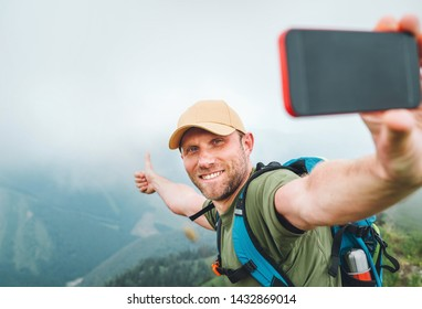 Young backpacker man taking selfie picture using smartphone and showing Thumbs Up during walking by the foggy cloudy weather mountain range .  Active sport backpacking healthy lifestyle concept.