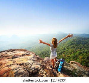 Young backpacker standing on top of a mountain and enjoying a morning valley view