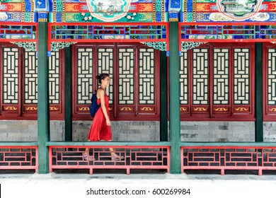 Young backpacker woman walking through old traditional long corridor at chinese temple, China summer travel. Asian girl visiting tourist attraction in Beijing.