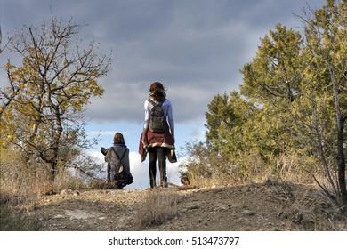 Young backpacker women enjoying mountain trip. Pretty caucasian girls hiking in mountains with backpack