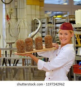 A young baker girl takes up her work in a bakery.  She poses for the camera and shows her various types of bakery workflows she tends to.
