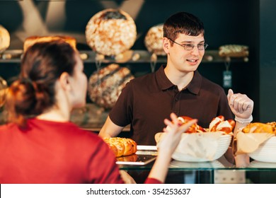 Young baker selling bread to woman