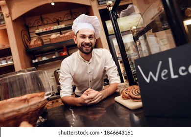 A young baker is standing and smiling at the camera in a cook hat. A baker stands behind a counter while an excerpt lies nearby.