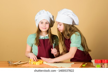 Young bakers following baking recipe. Small bakers rolling paste on kitchen table. Little girls baking cookies in baker shop. Kneading dough with baker flour.